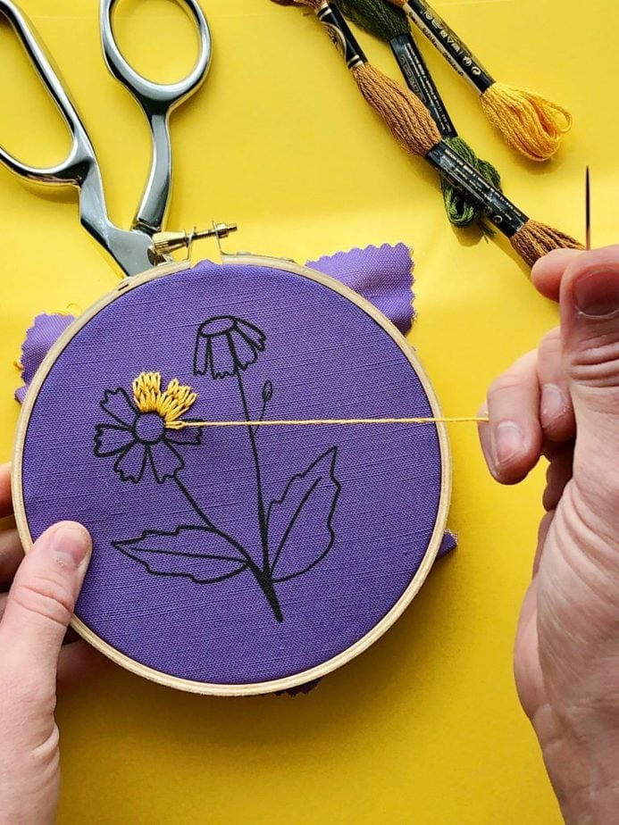 how to embroider - hand embroidering a flower onto fabric in an embroidery hoop