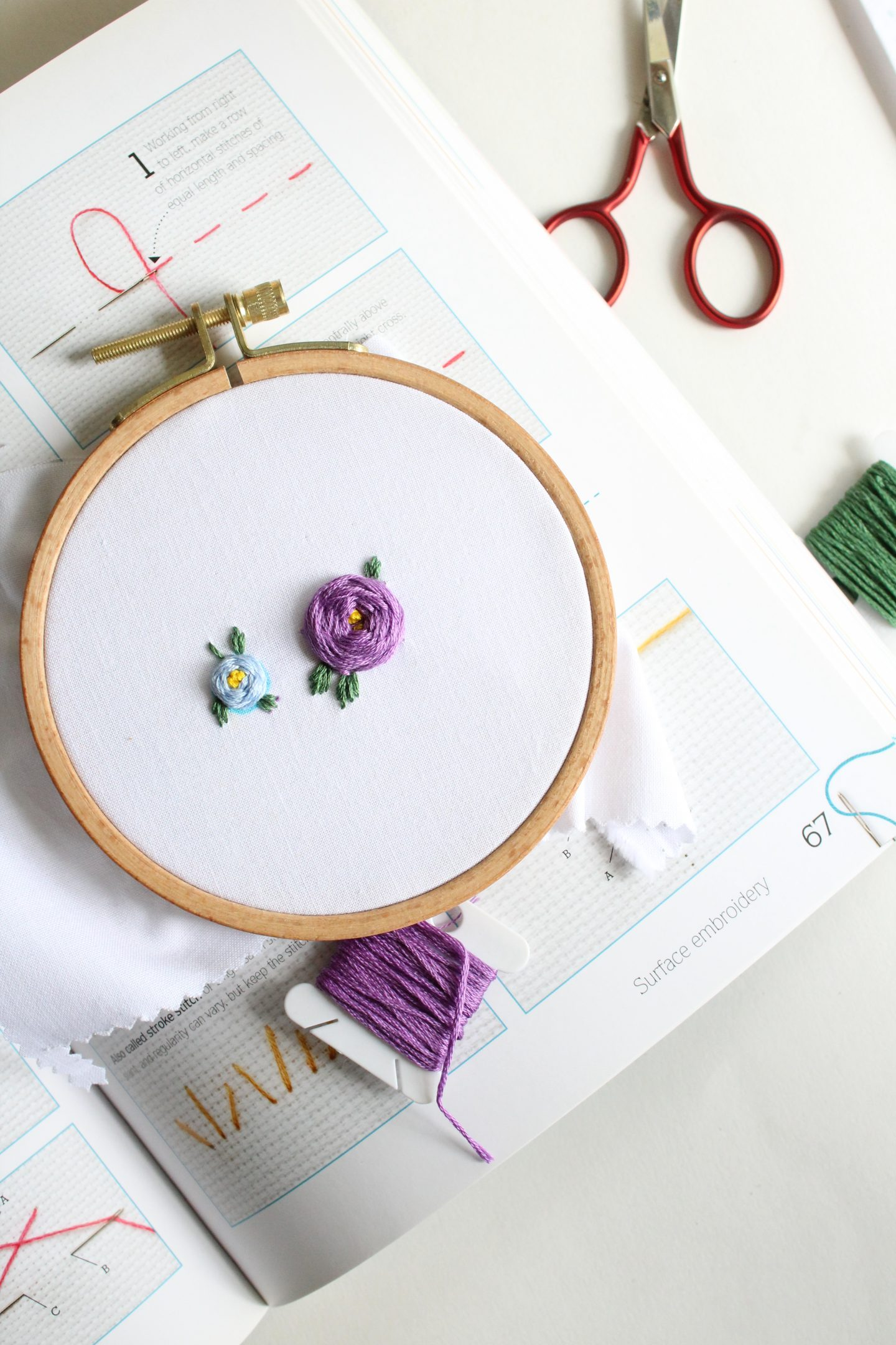 best embroidery books for beginners - picture of an embroidery hoop sitting on a book