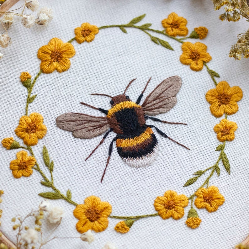 bee with a floral wreath around it